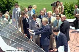 Jimmy Carter explains solar panels to reporters.