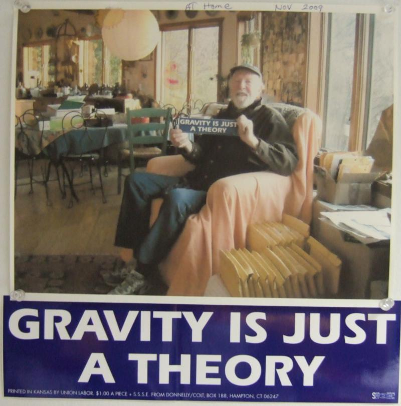 "Pete Seeger holding his ""Gravity is just a theory"" bumper sticker"