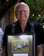 Vic Hutchison, holding a photo of the eponymic Anodonthyla hutchisoni