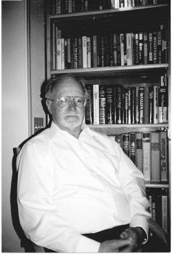 Photograph of Mark Perakh sitting in front of books