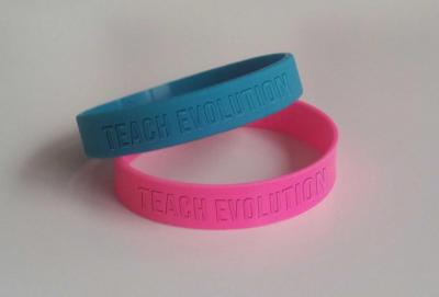 "Wristbands reading ""Teach Evolution"""