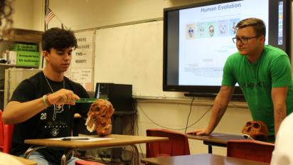 teacher with student who is measuring a skull
